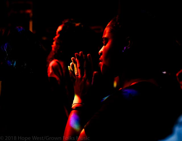 A prayerful member of the audience at the Tasha Cobbs Leonard Revival Tour