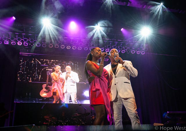 Peabo Bryson performing onstage in Atlanta with backup singer